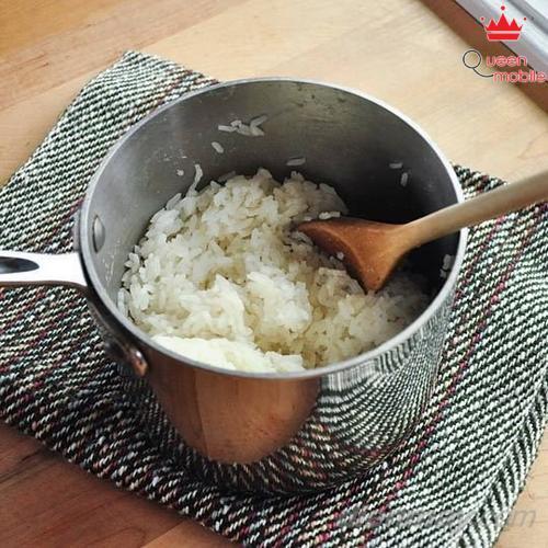 5. Sau khi nấu xong, tắt bếp và mở nắp, xới đều cơm bằng muỗng xới hay đũa, để yên khoảng vài phút cho bề mặt cơm khô ráo.