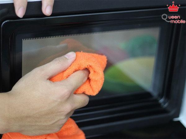 Dùng khăn lau sạch phần cửa kính của lò