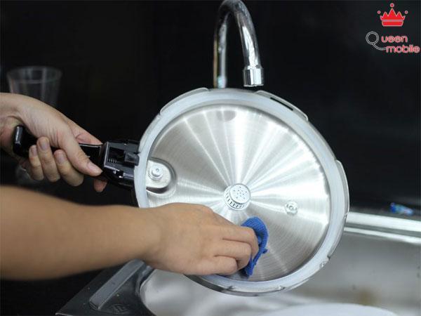Dùng khăn có chất tẩy rửa lau sạch vết dơ trên nắp nồi