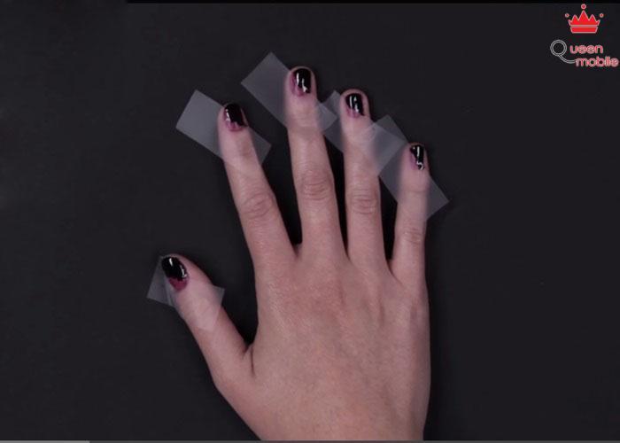 Dán băng keo chéo lên móng, sơn màu đen lên phần móng còn lại, chờ sơn khô lấy băng keo ra